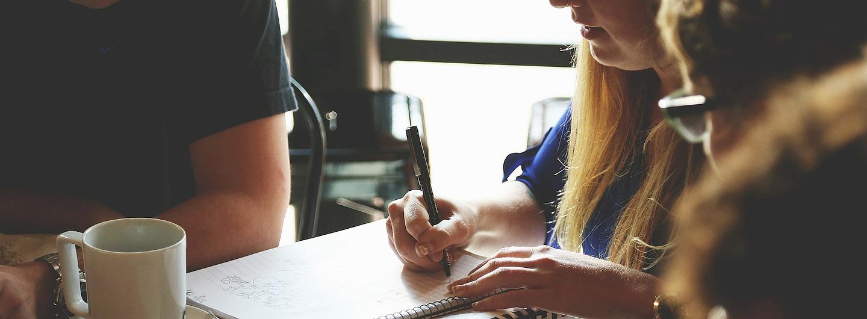 Frau macht Notizen in Lernrunde