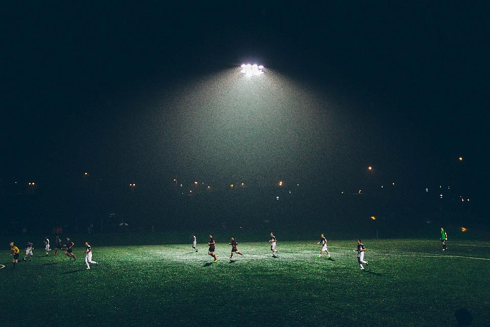 Fußballfeld bei Nacht, beleuchtet, Spieler