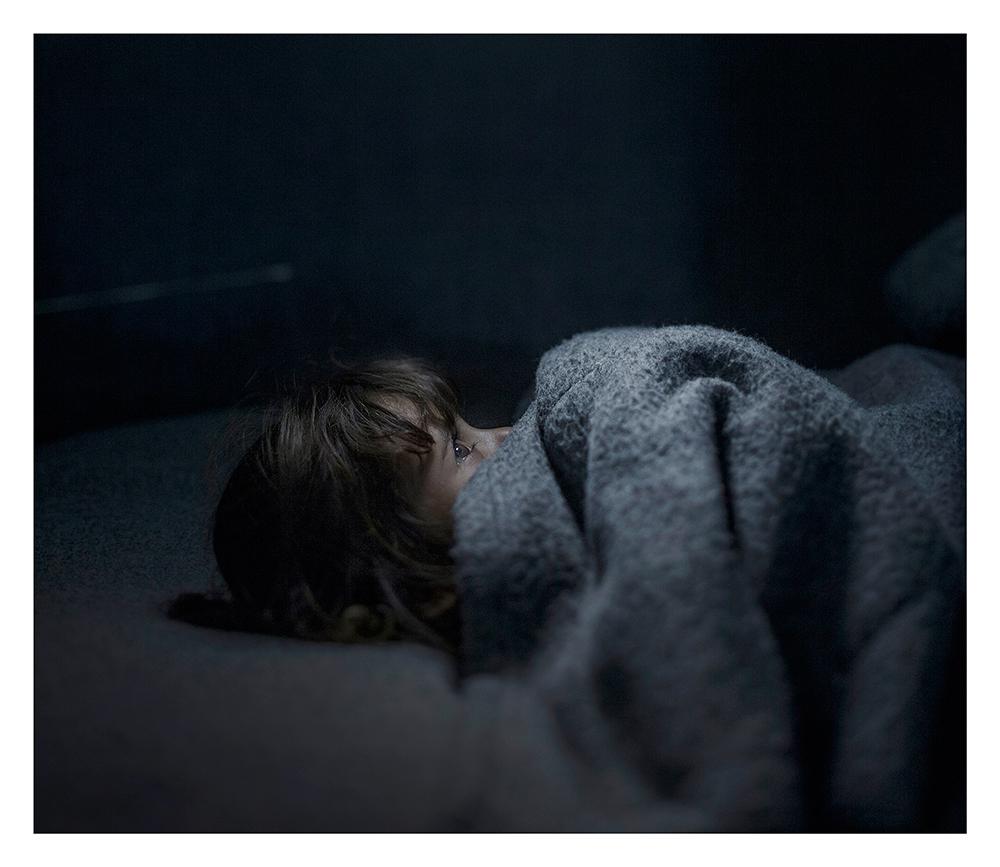 Ängstliches Flüchtlingsmädchen im Bett