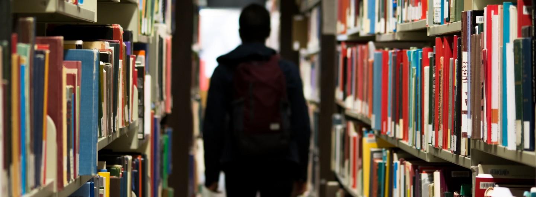 Mensch zwischen Regalen in einer Bücherei