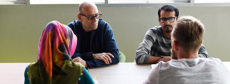 Vier Menschen unterhalten sich am Tisch