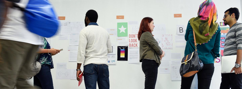 Menschen diskutieren vor einer Stelltafel