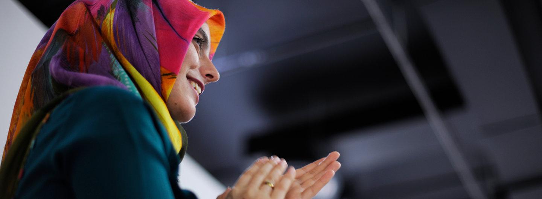 Frau mit Kopftuch applaudiert