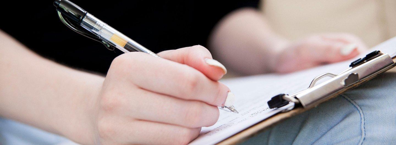 junge Frau macht sich Notizen auf einem Klemmbrett